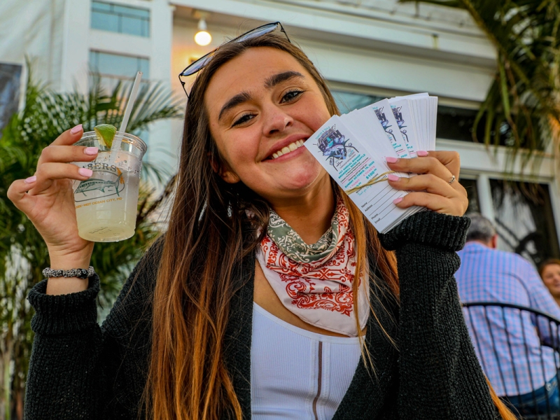 girl-smiling-holding-drink-and-tickets.jpg